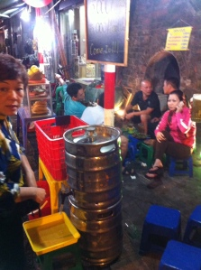 A Bia Hoi corner in the Hanoi Old Quarter. Note the hand dispenser at the bottom off the keg. 5,000 dong per glass = US $0.25.